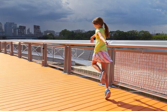 Skipping along the orange boardwalk at Newark Riverfront Park in Newark, NJ