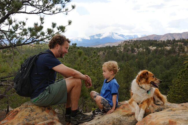 Father, son, and dog rest on a hike