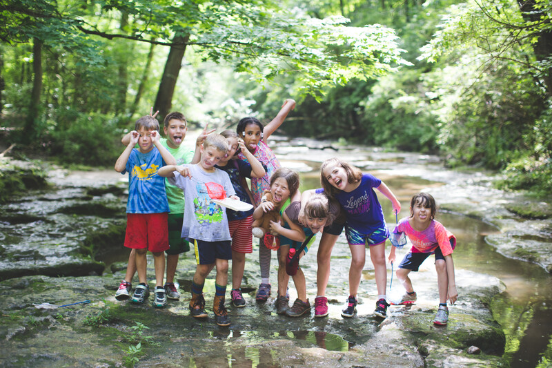A group of kids mug for the camera in a shallow creek