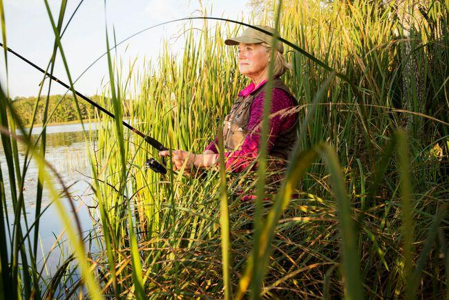 A woman casts a fishing rod along a reedy shorelin