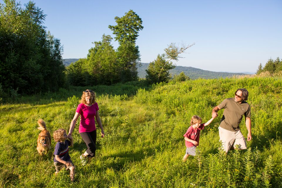 A family hikes on the Dowsville Headwaters property in Duxbury, VT.