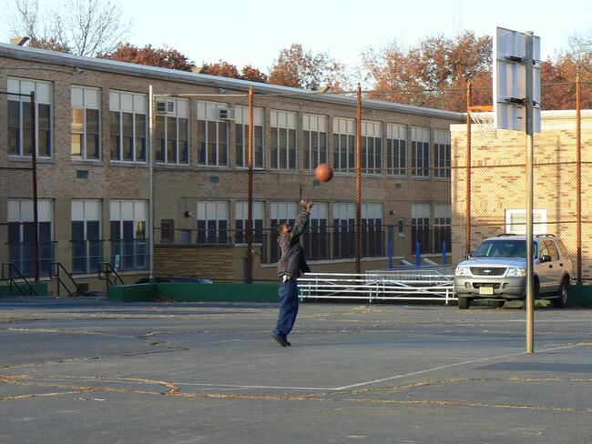 A boy plays basketball at a school in Newark