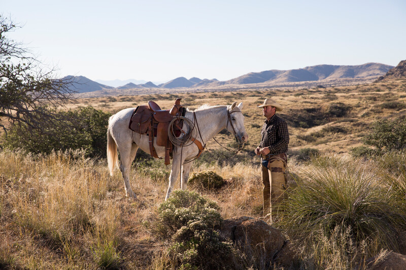 A man stands with his horse at Sky Island Grasslands - La Cienega Ranch in Southeastern Arizona,