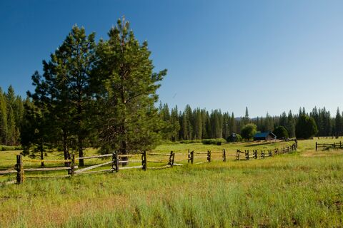 Split wood fence running through a meadow with a cabin and barn in the background