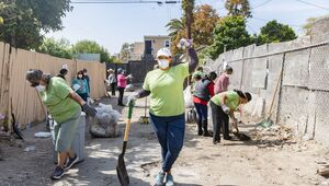 A woman wearing a dust mask stops to pose for the camera at a park clean-up