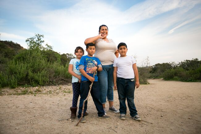 A mom and three kids on a trail