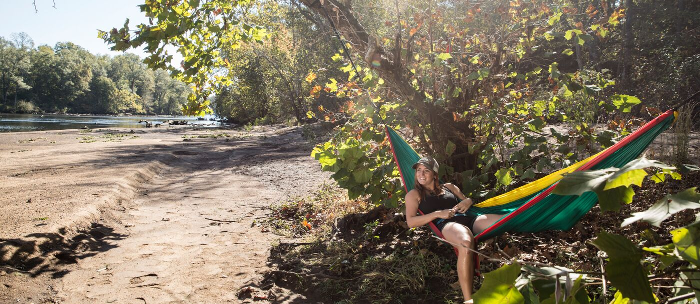 A woman in a hammock by a riverbank